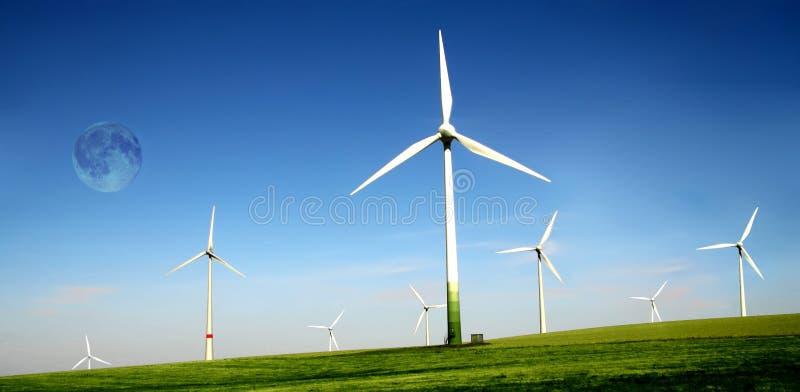 Azienda agricola delle turbine di vento con l'alta luna fotografia stock libera da diritti