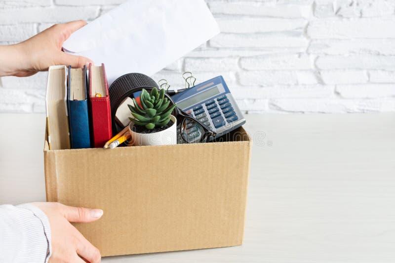 Azienda che trasporta i beni personali dell'azienda in cartone Concetto di licenziamento o di dimissioni immagine stock