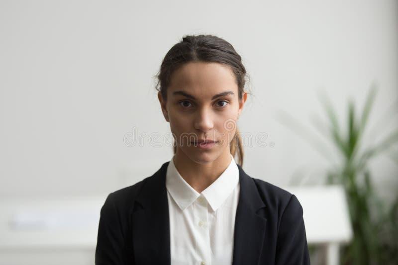 Azienda leader seria della giovane donna che esamina macchina fotografica, colpo in testa immagini stock