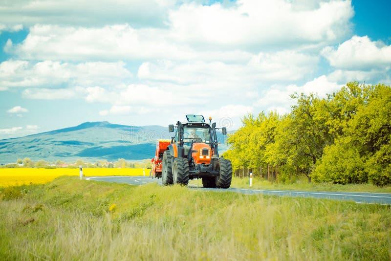 Azionamenti del trattore agricolo sulla strada fotografia stock