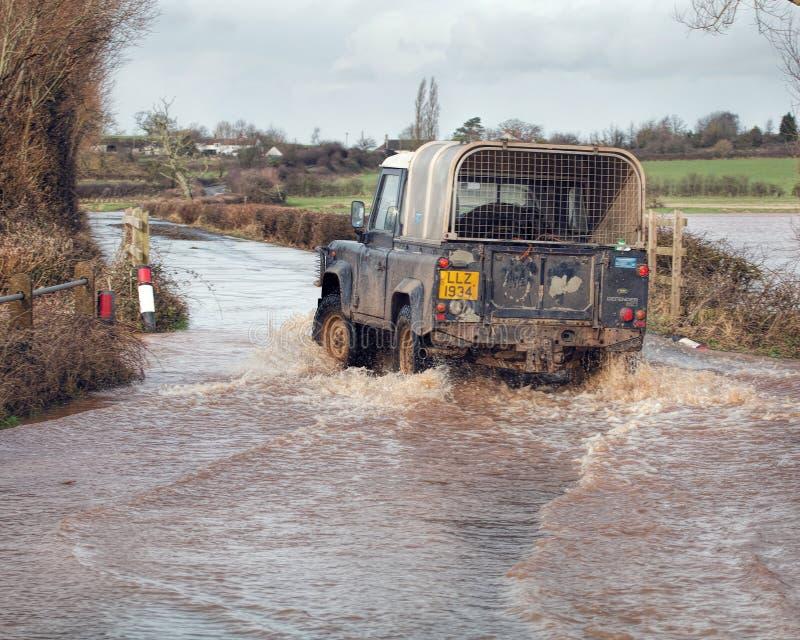 Azionamento di veicolo attraverso le acque di inondazione sulla strada immagini stock