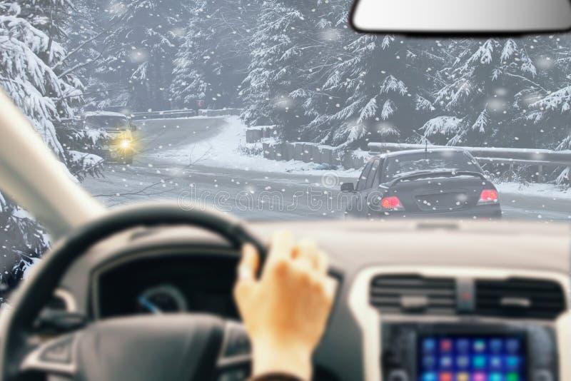 Azionamento ghiacciato di inverno della strada Termini di inverno sulla strada con il driver View della foresta immagini stock