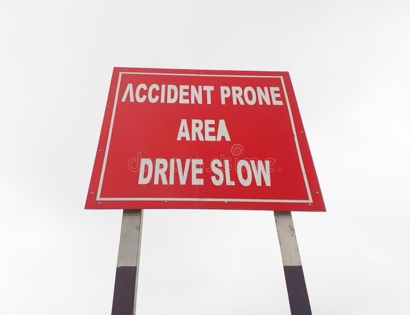 Azionamento lento, bordo soggetto ad incidenti sulla strada principale, bordo della strada del segno di area fotografia stock