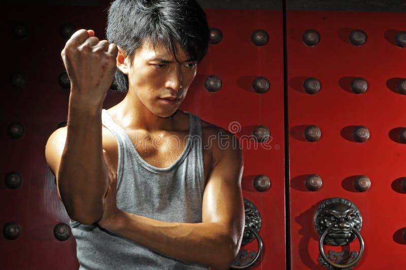 Azione asiatica di lotta intestina dell'uomo fotografia stock