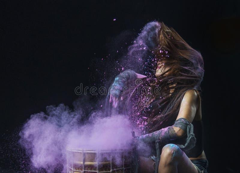 Azione di vibrazione di rullo del tamburo e dei capelli della spruzzata della polvere di colore dal giovane modello immagine stock