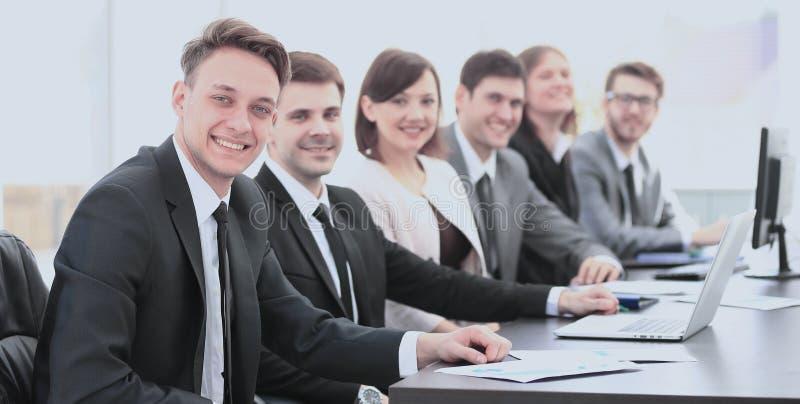 Azionisti del ` s della società ad una riunione sul lavoro, seduta ad una tavola fotografie stock