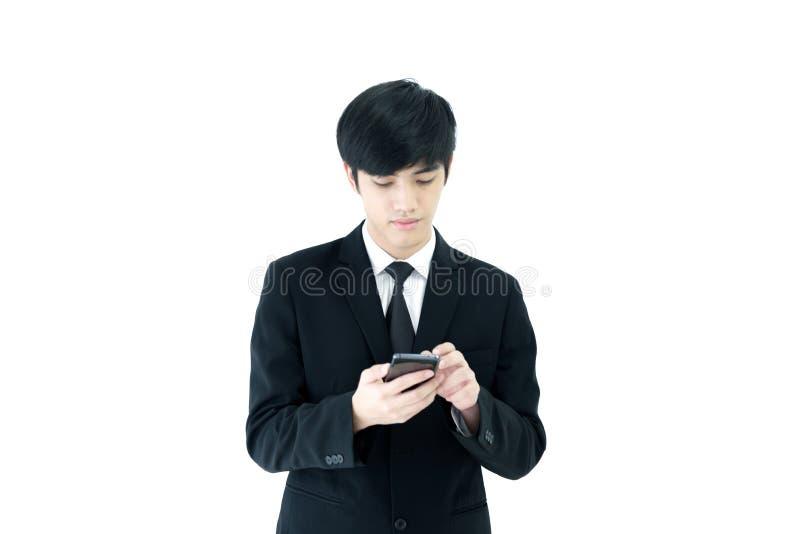 Azja biznesmen z czarnym kostiumem i czarnym krawatem używać telefon odizolowywającego na białym tle zdjęcia stock