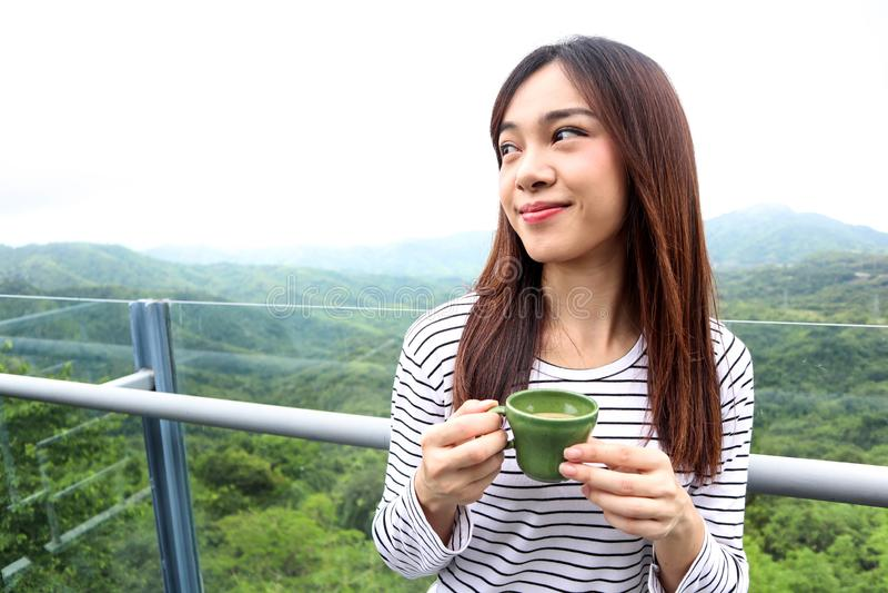 Azja kobieta cieszy się pięknego spokojnego ranek patrzeje niebo góry natury krajobrazu sceneria zaczyna nowy dzień pije kawę zdjęcia stock