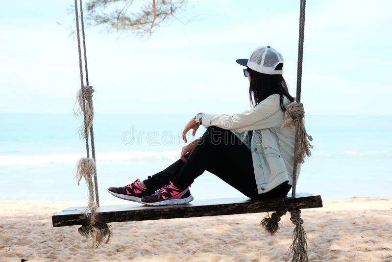 Azja kobieta siedzi samotnie na drewnianej krzesło arkanie na plażowym przyglądającym t obrazy royalty free