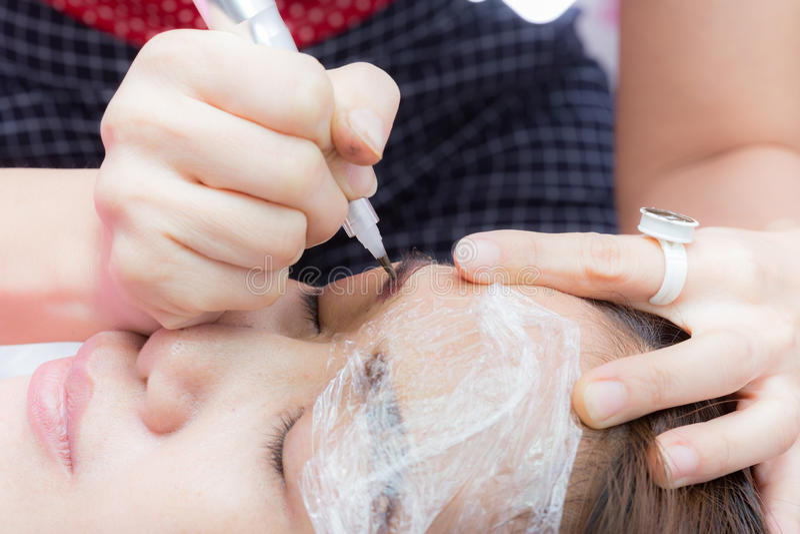 Azja kobieta stosuje stałego element uzupełniał brew tatuaż obraz royalty free
