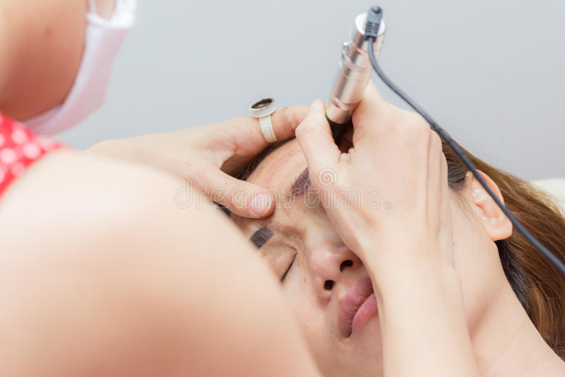 Azja kobieta stosuje stałego element uzupełniał brew tatuaż zdjęcia stock