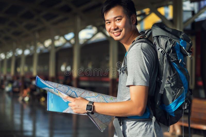 Azja mężczyzny mienia mapa z torba plecakiem samotnie w taborowym statio zdjęcie stock