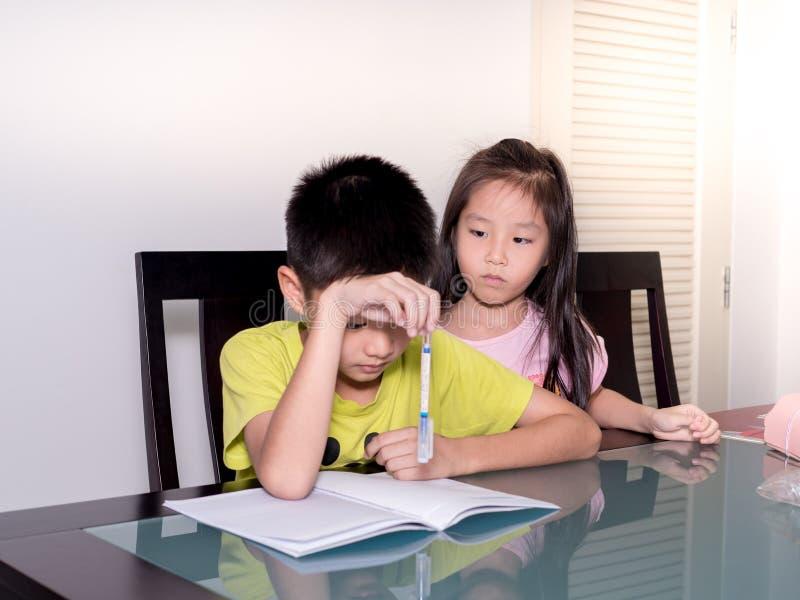 Azja mała siostra patrzeje jej brata studiuje jego pracę domową w domu i robi, obrazy royalty free
