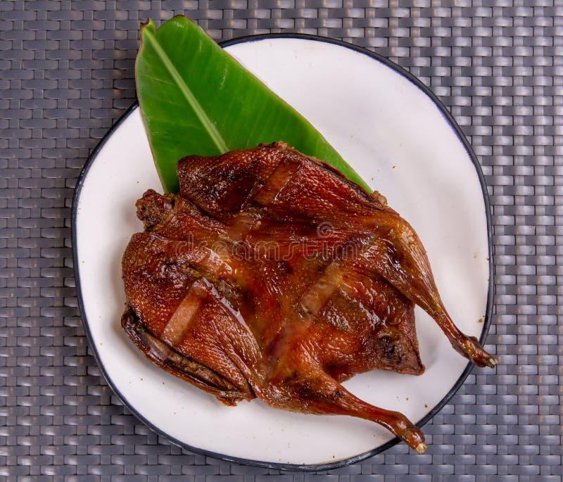 Azja Południowo-Wschodnia i Wschodnia: Typowe azjatyckie jedzenie, grillowana cała kaczka serwowana na talerzu zdjęcia royalty free