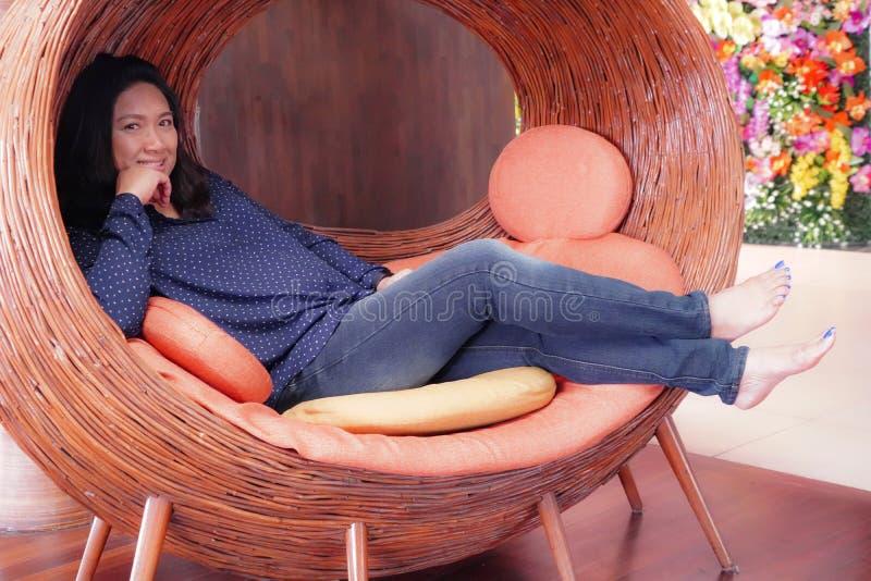Azja wieka średniego damy obsiadanie w czasu wolnego krześle przy kuluarowym hotelem obrazy royalty free