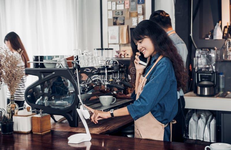 Azjata Barista używa pastylkę bierze rozkaz od klienta w sklepie z kawą, cukiernianego właściciela pisze napoju rozkazie przy kon zdjęcia stock