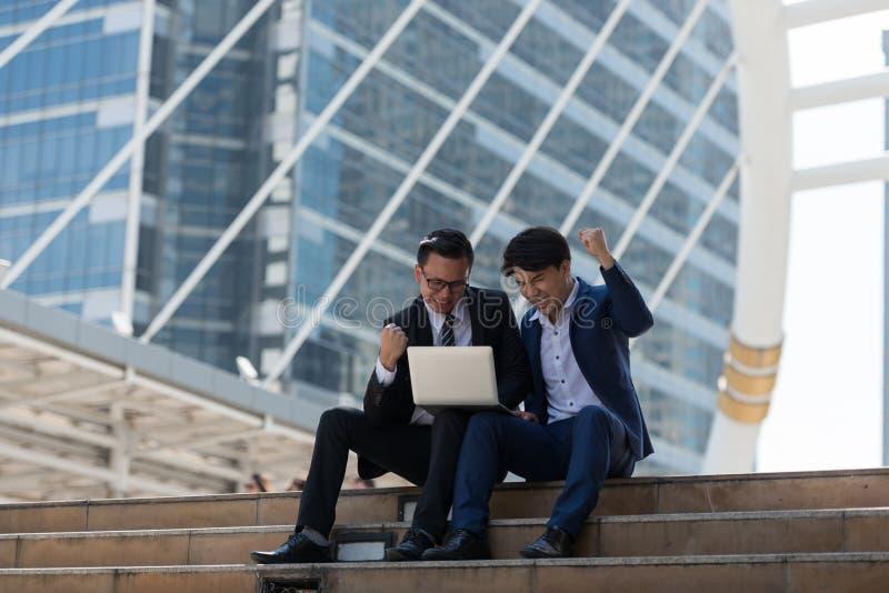 Azjata dwa biznesmen szczęśliwy podczas gdy będący usytuowanym widzii laptop w busi zdjęcia royalty free