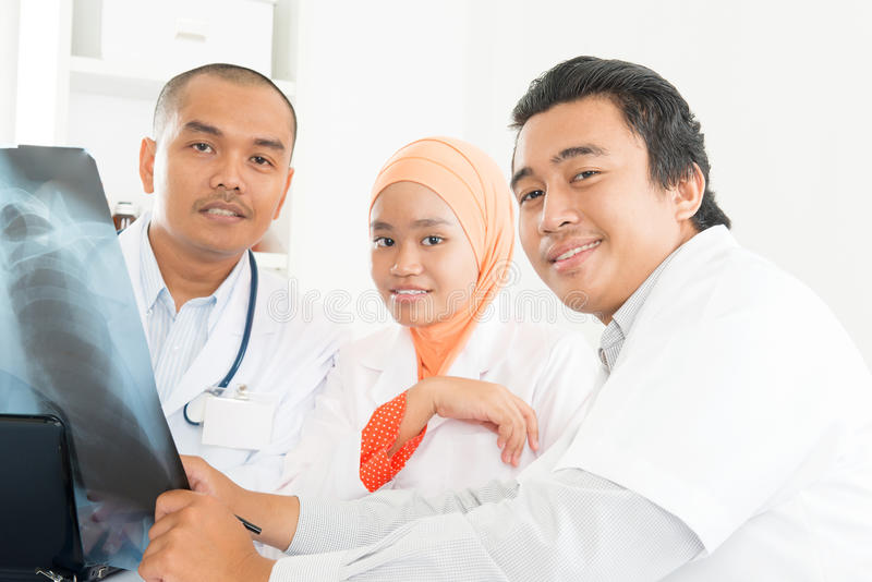 Azjata lekarki dyskutuje na promieniowanie rentgenowskie wizerunku obraz stock