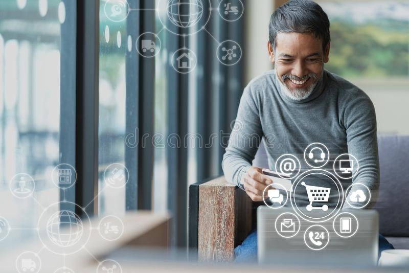 Azjata lub Latynoski mężczyzna używa płatniczego zakupy z ikona klienta sieci związkiem na ekranie online laptopu i karty kredyto fotografia stock