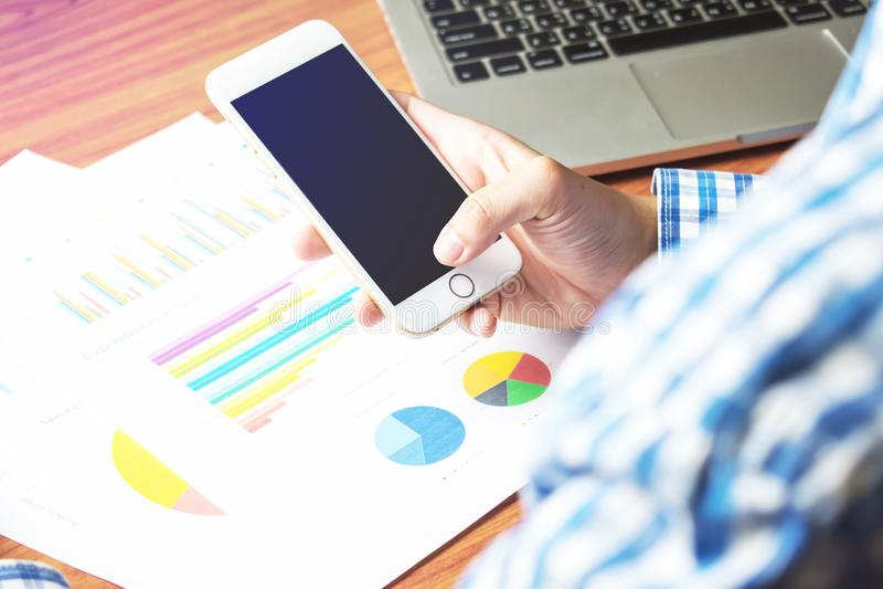 Azjata mężczyzna odzieży szkockiej kraty błękitne koszula Bawić się telefon i jest pracującym seriouslyon biurkiem kalkulator?w b zdjęcia royalty free