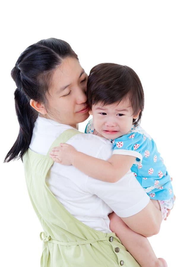 Azjata macierzysty przewożenie i koi jej córki na białym backgroun fotografia royalty free