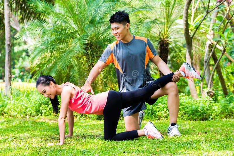 Azjata powozowa pomaga kobieta z rozciągań ćwiczeniami obrazy stock