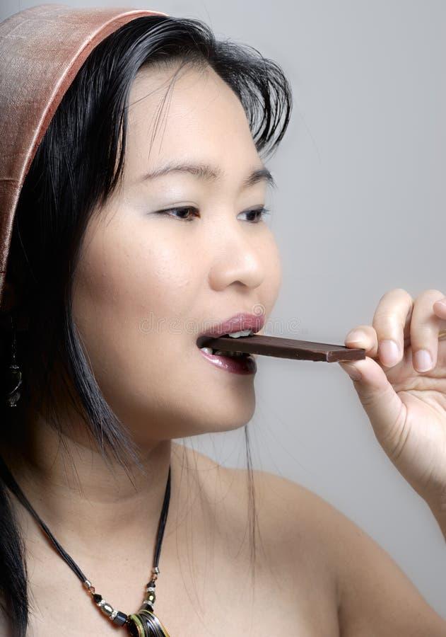 azjata prętowa czekoladowa łasowania kobieta obraz stock