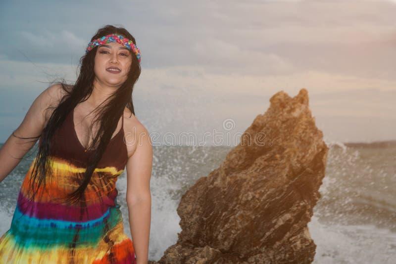 Azjatka plus rozmiar tłuszczu i nadwagi w kolorowych sukienkach stojących na skale na plaży fotografia stock