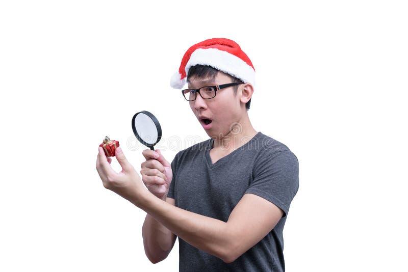 Azjaty Święty Mikołaj mężczyzna z eyeglasses i popielatą koszula gmeranie i patrzeć czerwonego prezenta pudełko z powiększać - sz zdjęcie stock