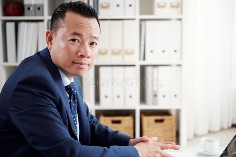 Azjaty dojrzały biznesmen pracuje przy biurem fotografia royalty free
