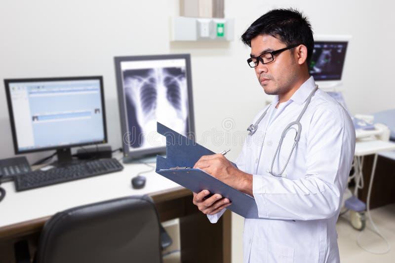 Azjaty pacjenta doktorskie pisze notatki lub recepta obrazy royalty free