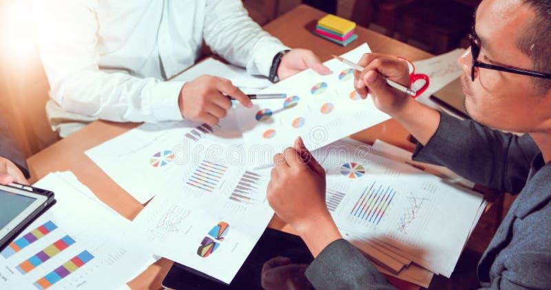 Azjatyccy biznesmeni i bizneswoman analizy dokumenty na biuro stole z pieniężnym diagramem pracuje wewnątrz laptopu i wykresu zdjęcia stock