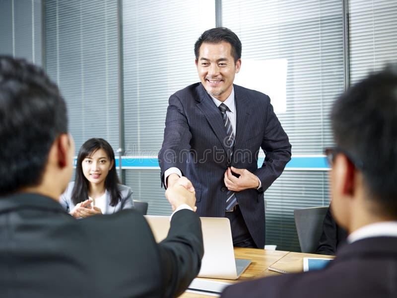 Azjatyccy biznesowi mężczyzna trząść ręki przed spotykać zdjęcia stock