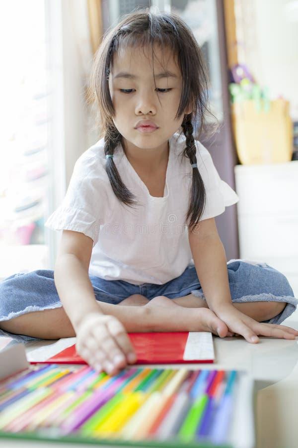 Azjatyccy dzieci bawić się koloru ołówek w hoime żywym pokoju zdjęcia royalty free