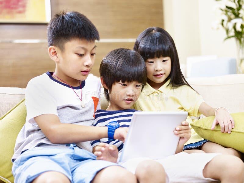 Azjatyccy dzieci używa cyfrową pastylkę wpólnie obraz royalty free