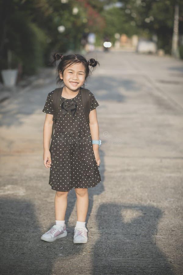 Azjatyccy dzieci z szkolnego plecaka toothy ono uśmiecha się plenerowy obraz royalty free