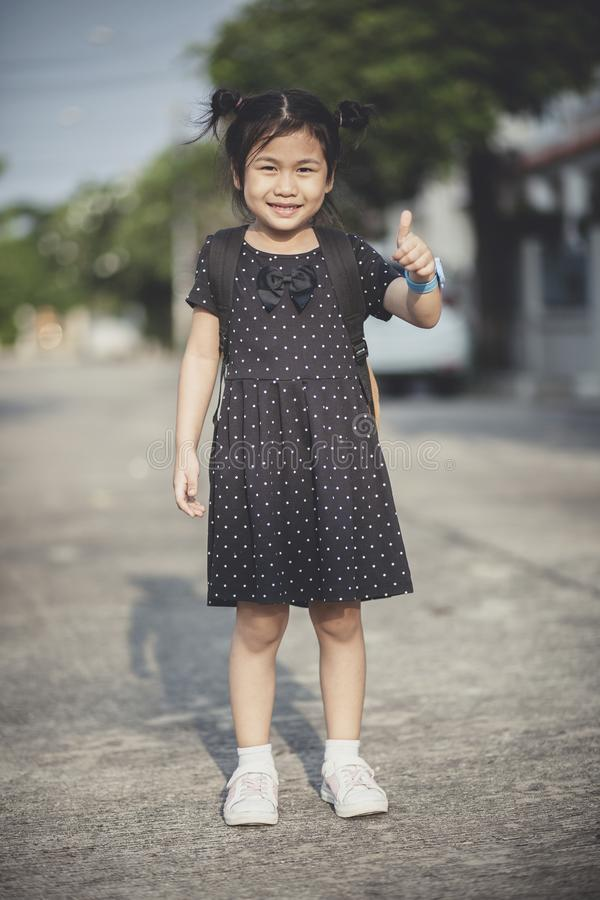 Azjatyccy dzieci z szkolnym plecak ręki znaka dobrym i toothy sm obraz royalty free