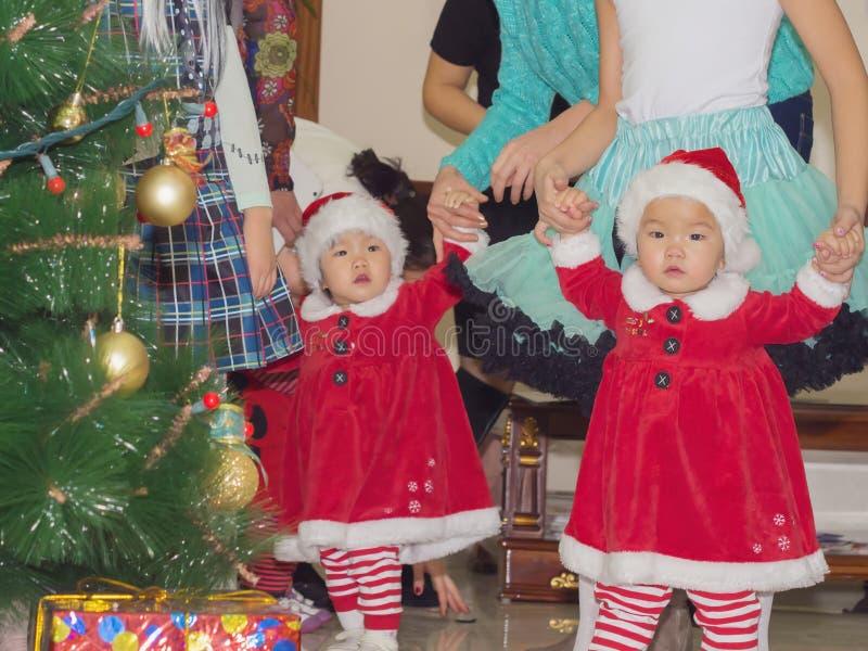 Azjatyccy dziecko dziewczynek bliźniacy wpólnie przy świętowań bożymi narodzeniami zdjęcie stock