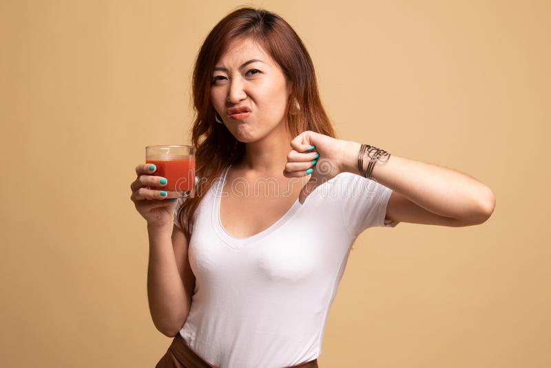 Azjatyccy kobieta kciuki zestrzelaj? nienawi?? pomidorowego sok zdjęcie stock