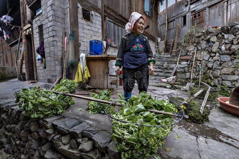 Azjatyccy kobieta rolnika Miao ludzie, stojaki w podwórzowy chłopski hous zdjęcie stock