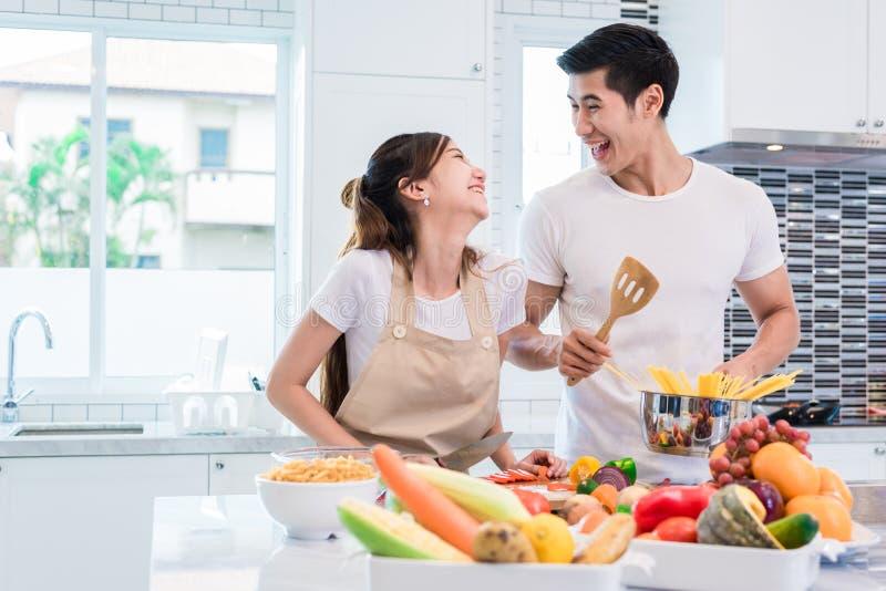Azjatyccy kochankowie lub pary gotuje w ten sposób śmiesznego w kuchennym dowcipie wpólnie zdjęcie stock