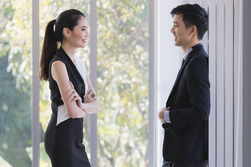 Azjatyccy ludzie biznesu opowiada wp?lnie w biurze zdjęcie stock