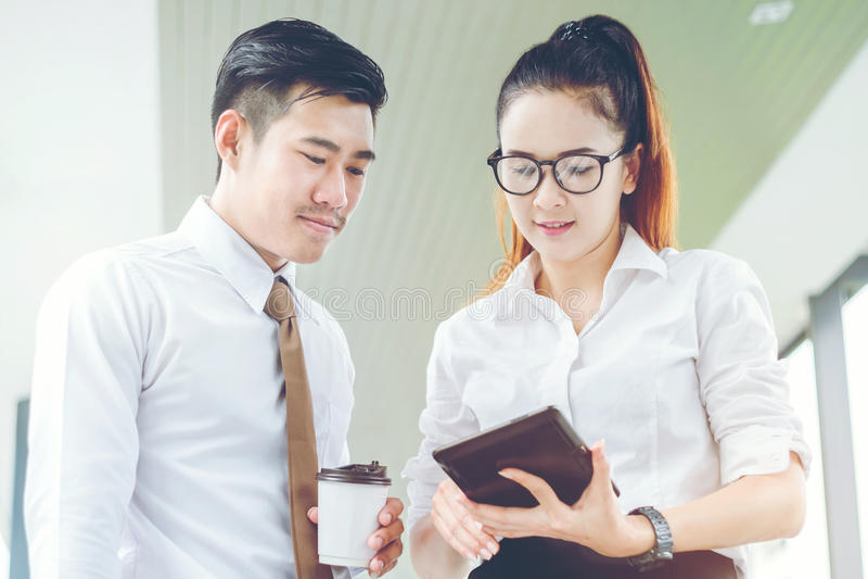 Azjatyccy ludzie biznesu używa cyfrową pastylkę plenerową po praca b obrazy stock