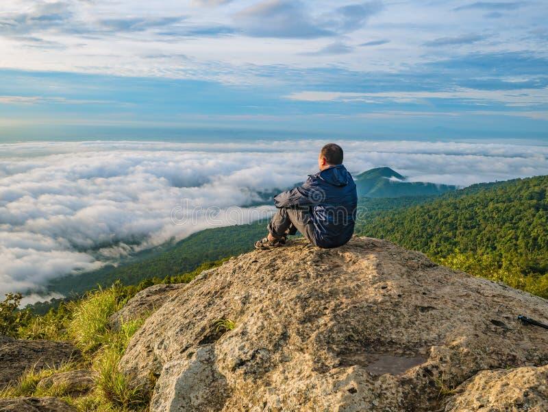 Azjatyccy mężczyźni Siedzą na falezie z pięknym niebem na Khao Luang górze w Ramkhamhaeng parku narodowym fotografia royalty free