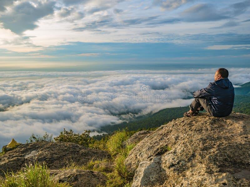 Azjatyccy mężczyźni Siedzą na falezie z pięknym niebem na Khao Luang górze w Ramkhamhaeng parku narodowym zdjęcie stock
