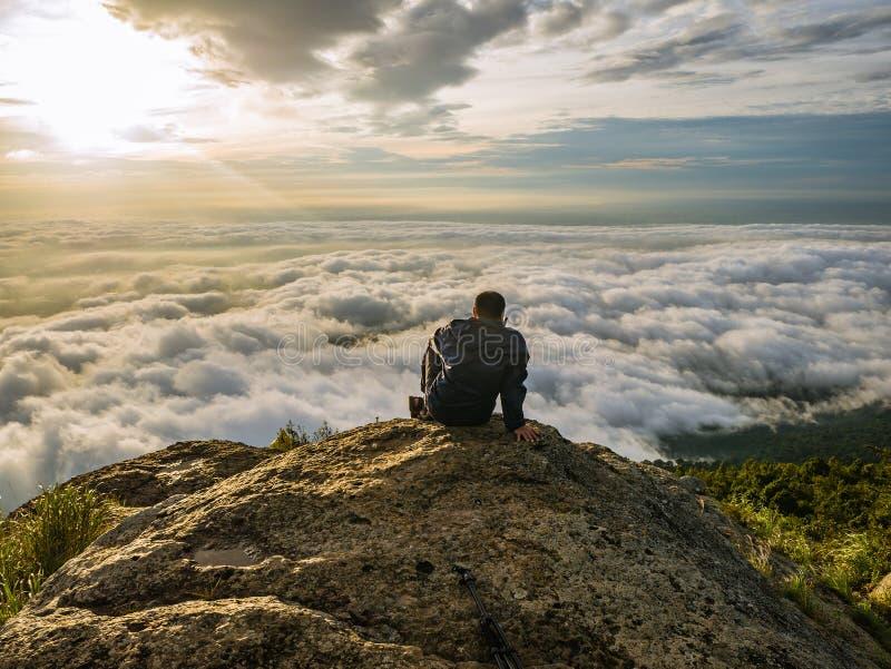 Azjatyccy mężczyźni Siedzą na falezie z pięknym niebem na Khao Luang górze w Ramkhamhaeng parku narodowym zdjęcia royalty free