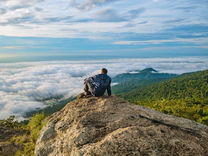 Azjatyccy mężczyźni Siedzą na falezie z pięknym niebem na Khao Luang górze w Ramkhamhaeng parku narodowym obrazy stock