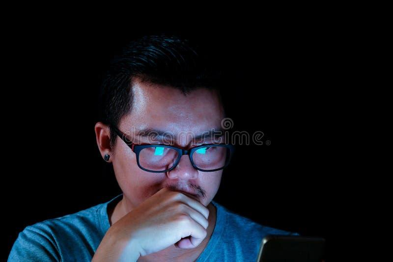 Azjatyccy mężczyzna używają pastylkę z błękitnym światłem lub telefon w ciemności obrazy stock