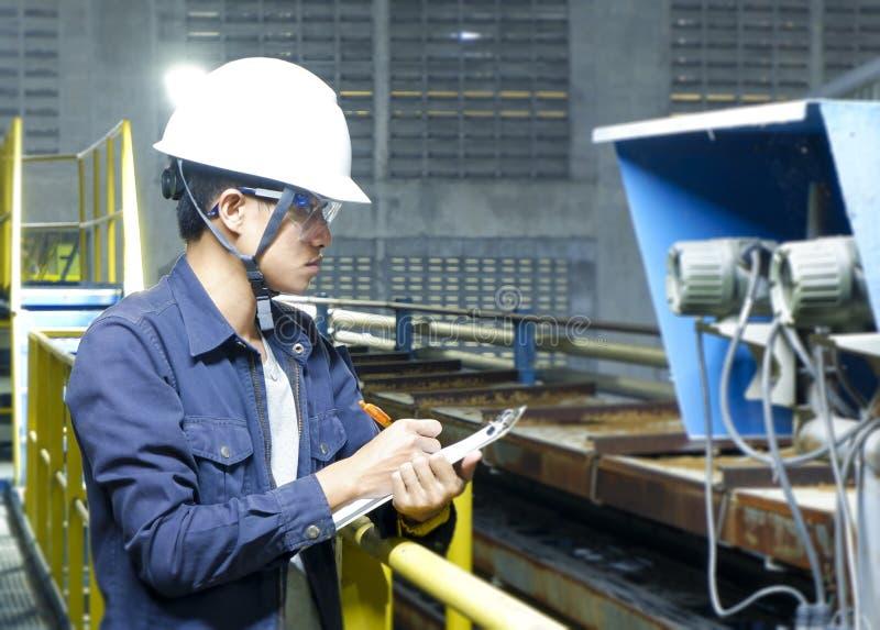 Azjatyccy młodzi człowiecy Sprawdzają maszynę wśrodku przemysłowej fabryki zdjęcie stock