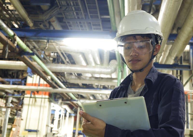 Azjatyccy młodzi człowiecy Sprawdzają maszynę wśrodku przemysłowej fabryki obrazy royalty free